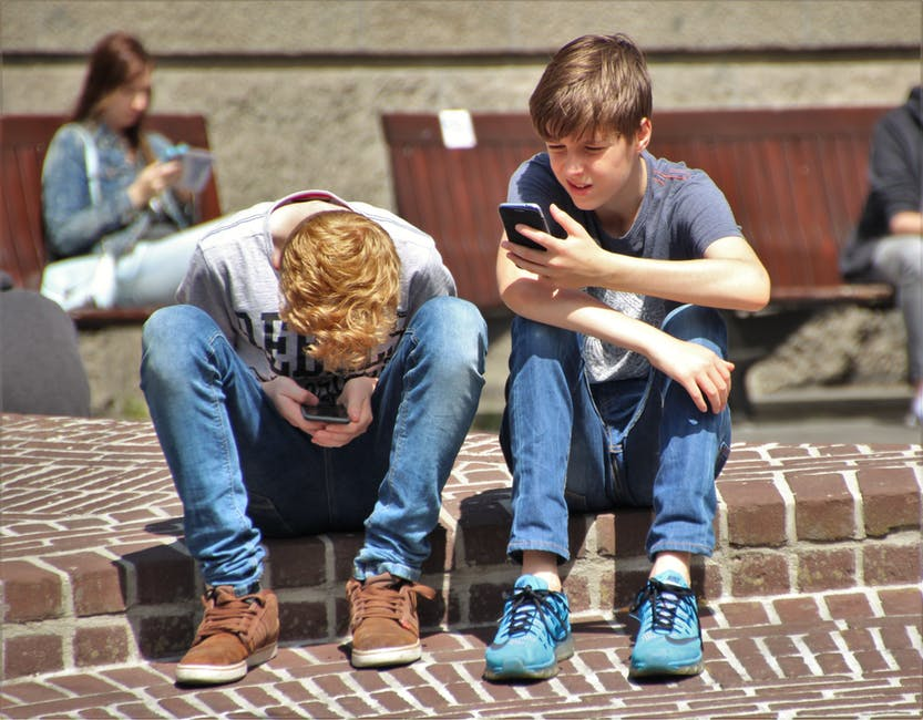Two boys playing on smart phones
